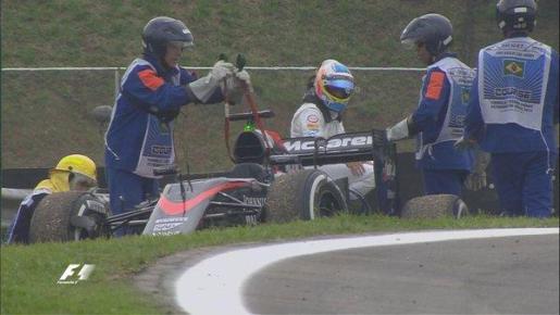 El piloto asturiano Fernando Alonso aguarda sentado en un guardarraíl que retiren su McLaren después de que ardiese el motor.