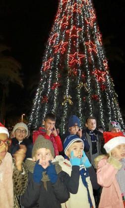 Niños cantando tras el encendido del árbol de Navidad.