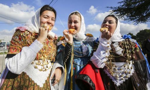 Tres payesas simpáticas prueban los buñuelos de Can Rei que se ofrecieron ayer en Forada. Foto: ARGUIÑE ESCANDÓN
