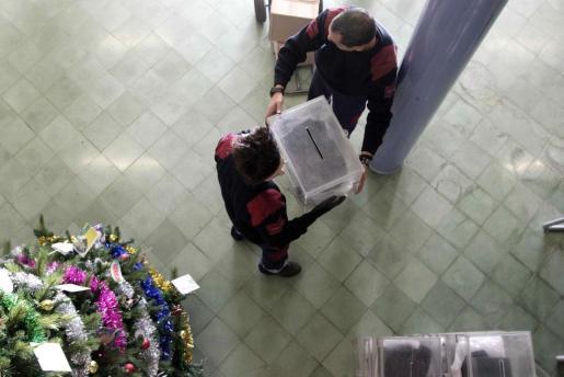 Dos trabajadores de los almacenes municipales de Barcelona colocan una urna en el instituto Menéndez y Pelayo.