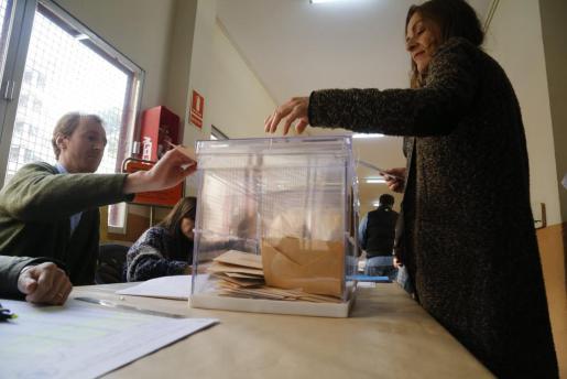 Una mujer deopista su voto en un colegio de Palma.