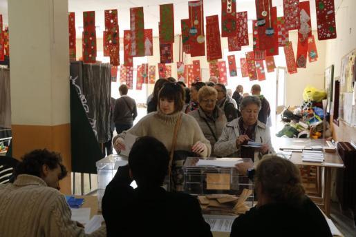 Una mujer deposita su voto en la urna en un colegio electoral de Palma.
