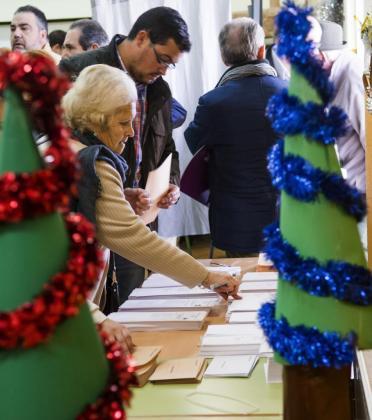 Una mujer elige sus papeletas en un colegio electoral del barrio sevillano de Triana.