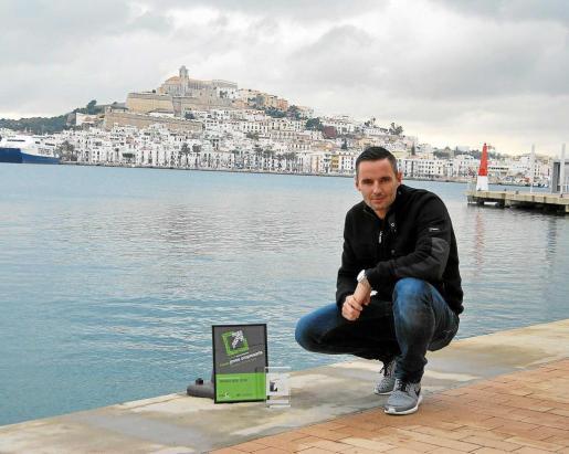 Marc Costa, junto a su premio de Joves Empresaris d'Eivissa i Formentera, posa en el puerto con Dalt Vila al fondo.