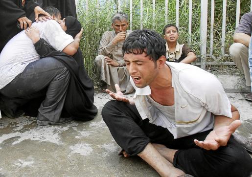 Un grupo de civiles llora desconsoladamente en el lugar del atentado suicida.