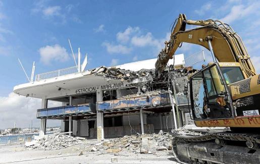 La máquina retroexcavadora empieza a derribar el inmueble en la plaza de es Martell donde se construirá un nuevo edificio.