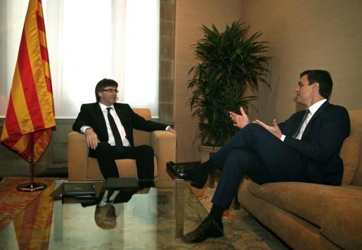El presidente de la Generalitat, Carles Puigdemont (i), y el secretario general del PSOE, Pedro Sánchez, durante su primera reunión este martes en el Palau de la Generalitat.