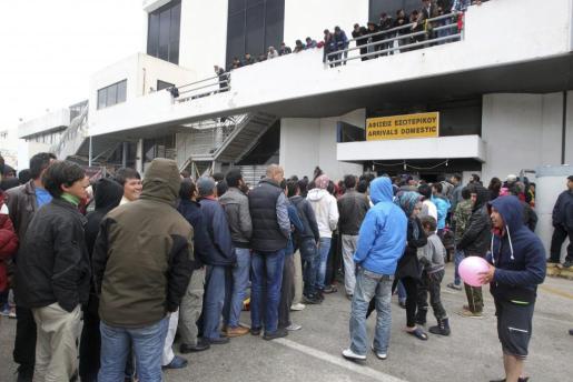 Refugiados procedentes de Turquía esperan para recibir comida en el antiguo aeropuerto de Elliniko, Grecia, ayer 14 de marzo de 2016.