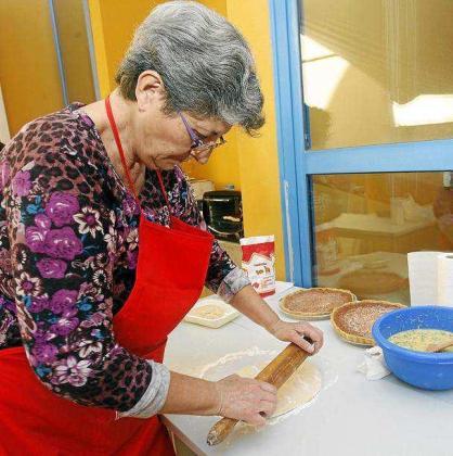 Dolores Costa durante la elaboración de los 'flaons' en los talleres del año pasado. Costa recordaba la importancia de que la masa quede muy bien extendida y por tanto fina antes de poner sobre ella el relleno de queso, azúcar, huevos, levadura y un poquito de ralladura de limón.