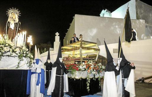 La cofradía del Cristo Yacente discurrió con su imagen dentro de una urna de cristal en forma de féretro y con sus miembros vestidos con túnica negra y capa blanca. Foto: A. ESCANDÓN