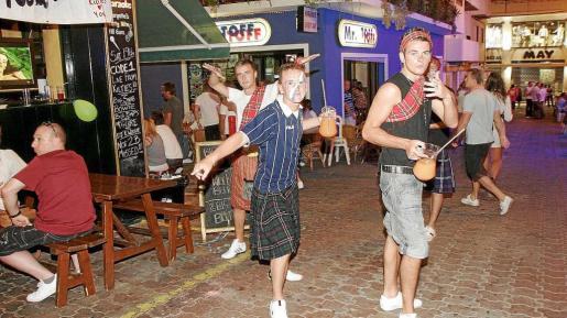 Dos jóvenes portando jarras de bebida en plena calle del casco urbano de Sant Antoni.