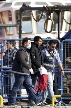 Policías escoltan a los refugiados que llegan al puerto de Dikili en Izmir (Turquía) provenientes de la isla de Lesbos.