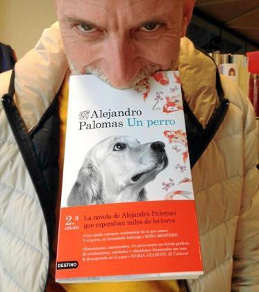Alejandro Palomas aguanta con la boca una edición de su última novela 'Un Perro', como si de un can se tratara.
