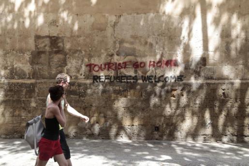 Una pareja de turistas pasa junto a una pintada.