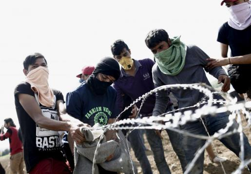 Refugiados tiran de una alambrada de espino durante una protesta para pedir la apertura de la frontera en el campo de refugiados de Idomeni.