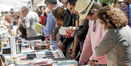 Decenas de personas ojean diversos ejemplares de los libros expuestos ayer en el paseo Vara de Rey de Vila. Foto: DANIEL ESPINOSA