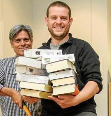 Cargado con libros. Pedro González posó divertido con los libros de Districte Hipérbole mientras Mateo le ayudaba. Foto: TONI ESCOBAR