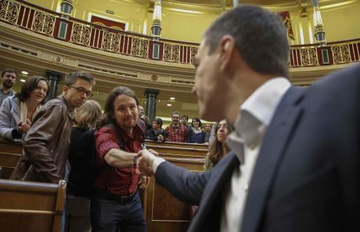 El secretario general del PSOE, Pedro Sánchez (d), y el líder de Podemos, Pablo Iglesias, se estrechan la mano al finalizar en el Congreso de los Diputados el último pleno de la XI Legislatura.
