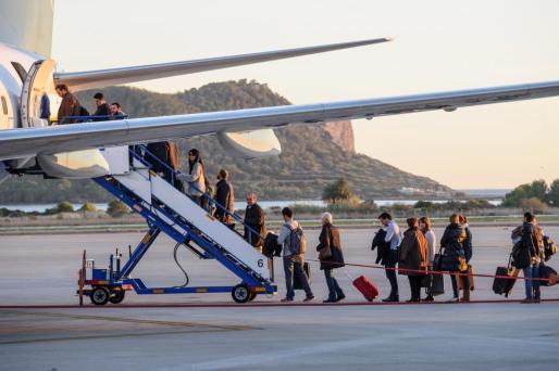 Viajeros subiendo la escalerilla de un avión en el Aeropuerto de Ibiza.