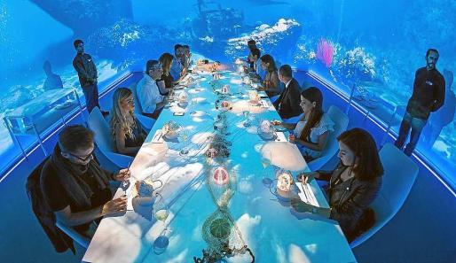 Imagen de un grupo de doce comensales disfrutando de una cena espectáculo en Sublimotion.