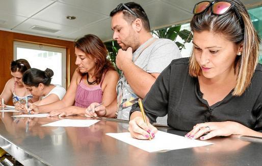 Diferentes trabajadores del centro Cas Serres firmando el manifiesto que entregaron en el Consell.