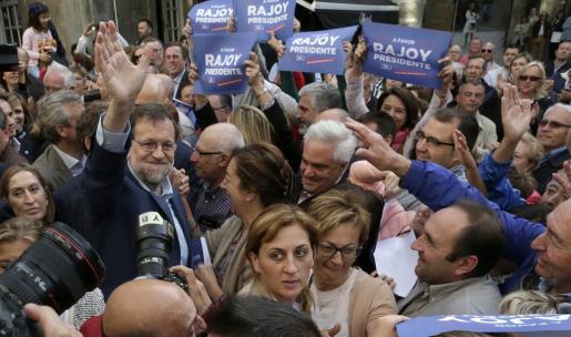 El presidente del Gobierno en funciones y candidato por el PP a la reelección, Mariano Rajoy, saluda a los simpatizantes que le aclamaban en Pontevedra.