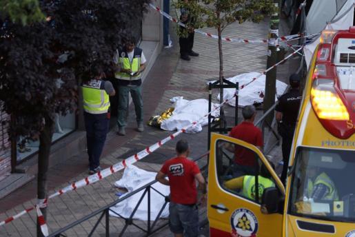 Los cadáveres de las tres personas halladas muertas tras un incendio registrado esta tarde en un despacho de abogados de Madrid permanecen tendidos en la acera a la espera de la llegada del juez. Todo los fallecidos presentaban signos de muerte violenta. Foto: Javier Lizon