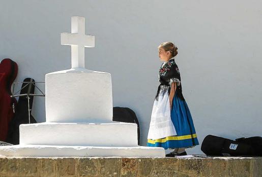 Una niña de l´Aljama de Bétera frente a la cruz de la iglesia y los joaners disfrutando de la celebración del día del patrón de su pueblo. Foto: TONI ESCOBAR