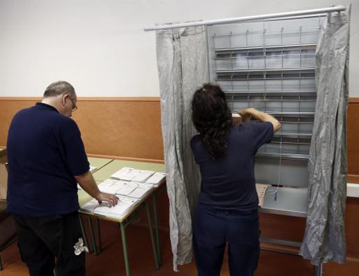 Operarios del Ayuntamiento de Pamplona colocan en un colegio electoral de la capital navarra las urnas y papeletas correspondientes para que los ciudadanos puedan ejercer su voto en las elecciones generales.