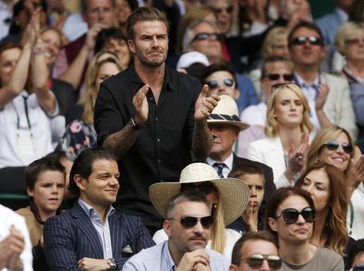 David Beckham, acompañado por sus hijos Romeo y Cruz, aplaude una jugada en la pista central de Wimbledon.