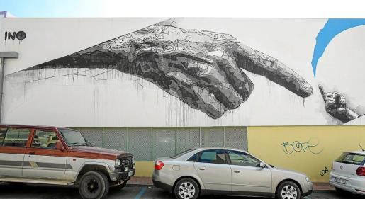 El grafiti es una obra realizada por el artista INO, y se sitúa en la fachada del centro educativo Vara de Rey en el municipio de Sant Antoni. La polémica se suscita ante la posición del dedo.