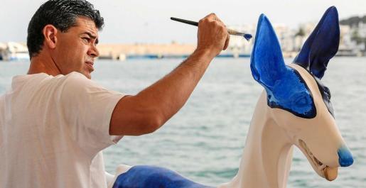 Miguel Ángel García pintando su podenco. Foto: TONI ESCOBAR