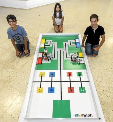 María Pilligua, Pau Albiñana y David Ripoll junto a sus robots y la pista.