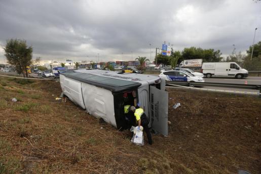 Efectivos de la Guardia Urbana inspeccionan el autobús que transportaba a turistas alemanes que se dirigían al aeropuerto y que ha volcado esta madrugada en la ronda litoral de Barcelona.