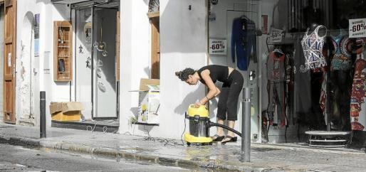 Una comerciante, limpiando y achicando agua de su local. Foto: A. ESCANDÓN