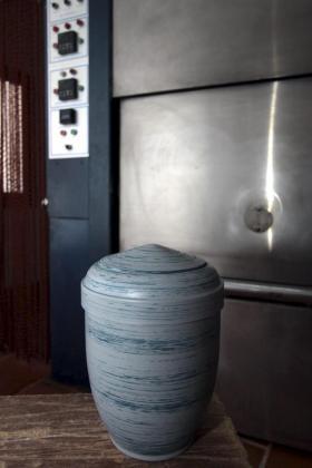 Una urna frente a un horno crematorio.