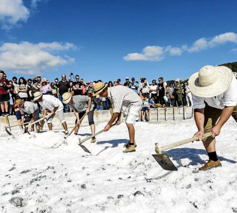 Un grupo de salineros enseñan a los visitantes el modo de recoger la sal de manera manual.