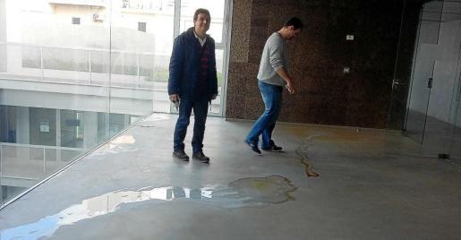 El director y el jefe de estudios muestran los charcos de agua procedentes de las goteras.