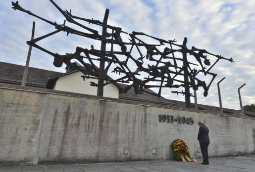 La canciller alemana Ángela Merkel depositando una corona de flores en un memorial en el campo de concentración de Dachau (Alemania).