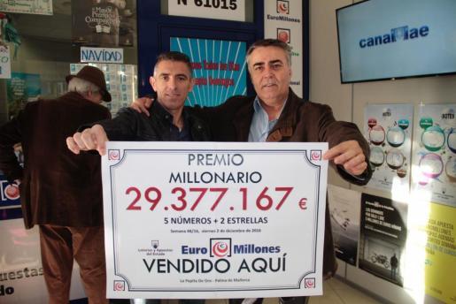 Los propietarios de la administración posa con el cartel que anuncia el premio del Euromillón de este viernes.