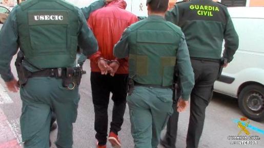 Agentes de la Guardia Civil custodian a uno de los doce detenidos en el marco de la operación 'Posidonia'.