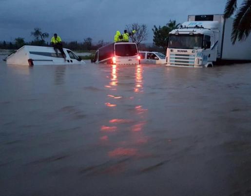 El fuerte temporal que azota Mallorca ha dejado imágenes sorprendentes en la Isla. En la imagen, diversos vehículos, incluido un furgón de la Guardia Civil, están atrapados en una carretera de Campos.
