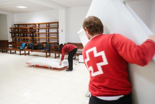 Los voluntarios de Cruz Roja colocan colchones para que los sin techo puedan dormir en estos días de intenso frío. Foto: TONI ESCOBAR