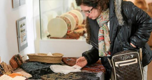 Una mujer observa los mantones y pañuelos expuestos en el Molí d'en Simó.