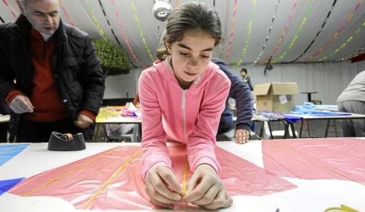 Una niña trabaja en su cometa. Foto: DANIEL ESPINOSA