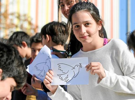 Una estudiante del colegio público Can Misses de Ibiza sostiene un cartel con el tradicional símbolo de la paz: la paloma volando con una rama de olivo en el pico.