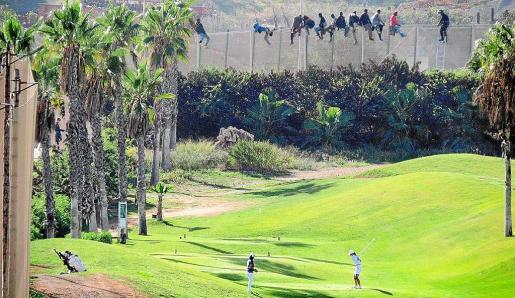 La famosa fotografía de la valla de Melilla repleta de inmigrantes mientras al lado se sigue jugando al golf.