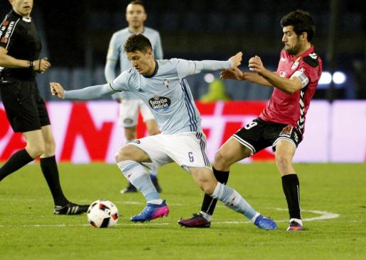 El centrocampista serbio del Celta de Vigo Nemanja Radoja pelea un balón con el centrocampista del Alavés Manu García duante el partido de ida de semifinales de la Copa del Rey que ambos equipos juegan en el estadio de Balaídos de Vigo.
