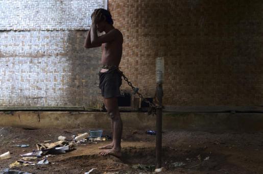 Un enfermo mental indonesio permanece encadenado a un poste en el patio trasero de su vivienda en la localidad de Lawang.