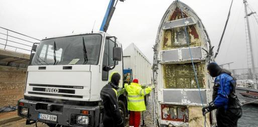 Un grupo de voluntarios sacan una barca que estaba hundida en el puerto de Sant Antoni con la ayuda de una grúa.